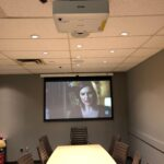 """A 92"""" motorized screen automatically drops down when the system is turned on."""
