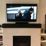 """Mopounted a 65"""" TV over the fireplace and seamlessly integrated their Sonos soundbar in without any wires showing."""
